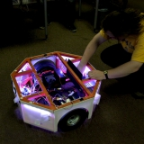 Колесная база, созданная в Нейроботикс, держит 200 кг нагрузки. Содержит в себе аккумуляторы и нетбук, который управляет Алисой.